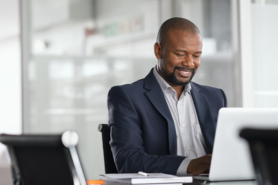 Black mature businessman working on laptop
