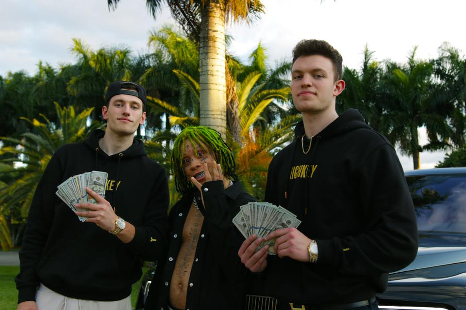 Three young men in front of a car and palm tree, holding fans of hundred-dollar-bills