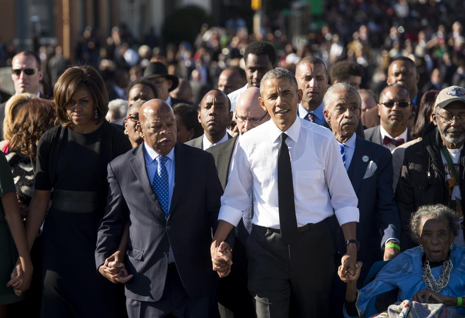 President Barack Obama, First Lady Michelle Obama (L), and US Representative John Lewis (2nd-L), Democrat of Georgia cross the Edmund Pettus Bridge to mark the 50th Anniversary of the Selma to Montgomery civil rights march (Photo credit: SAUL LOEB/AFP via Getty Images)