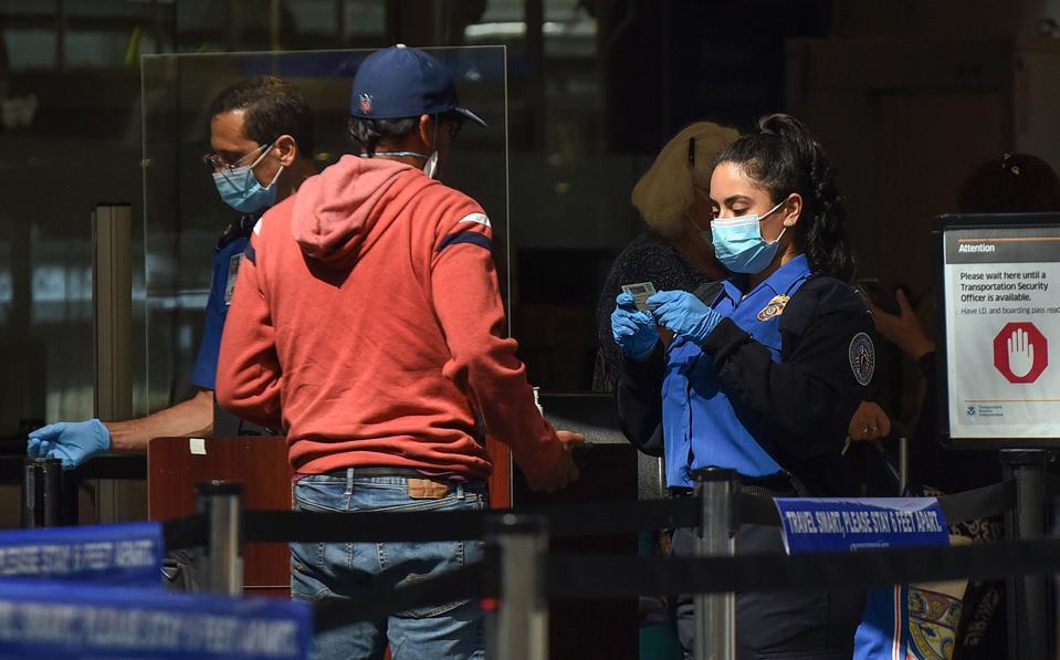 A TSA officer checks a man's ID at a screening checkpoint at...