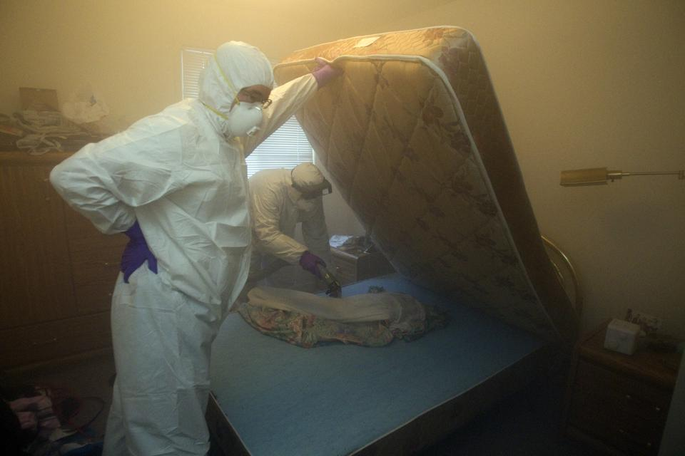 Christian Cadieux (R), owner of Bed Bugs Bite fumigates a mattress as part of their process to get rid of bed bugs.