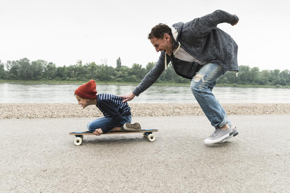 Happy father pushing son on skateboard