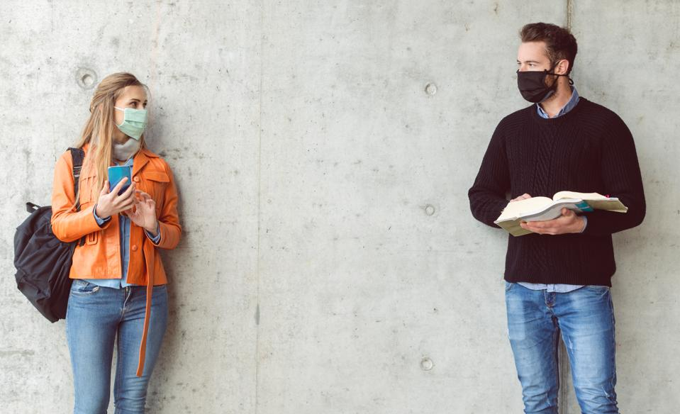 Two students standing in social distance wearing face mask