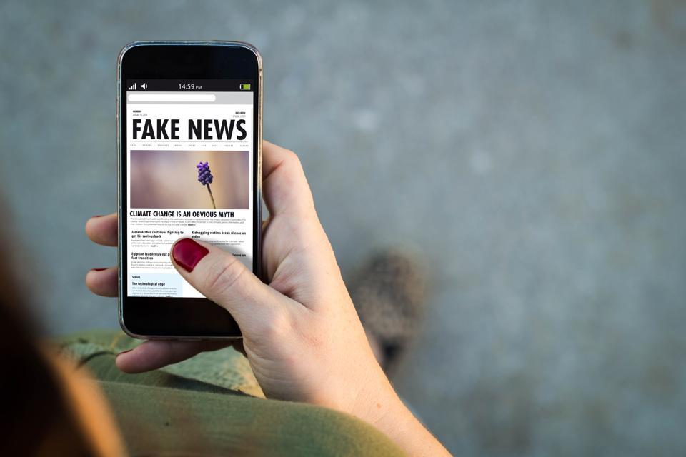 Woman walking smartphone fake news
