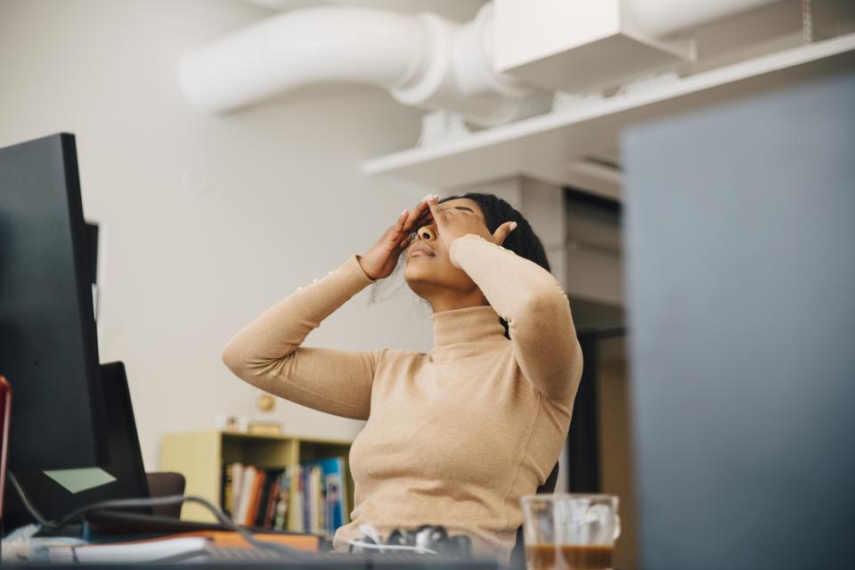 Frustrated female computer programmer with head in hands sitting in creative office