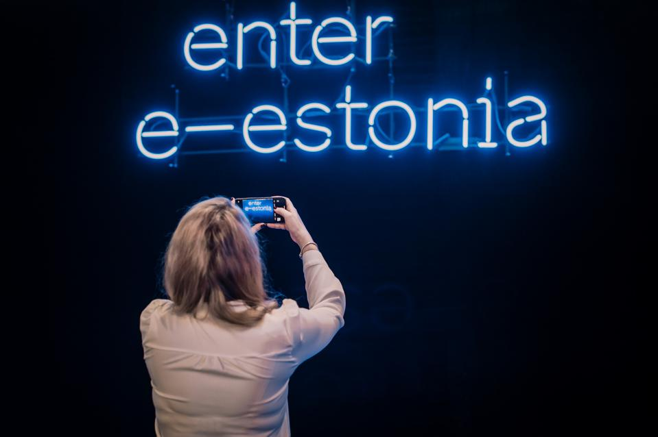 Woman taking a picture of neon sign greeting visitors to E-Estonia offices