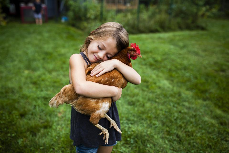 Smiling girl with eyes closed holding hen while standing in yard