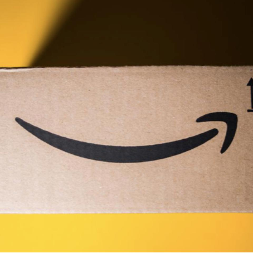 Amazon's Cardboard box against yellow with smile logo on it