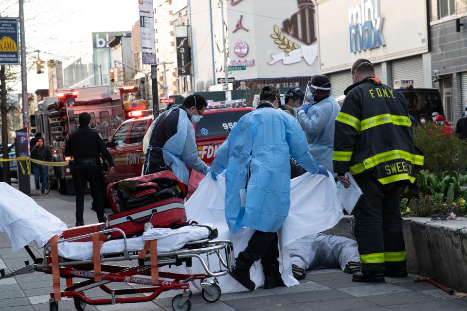 Paramedics cover a body of a man who died after collapsing...