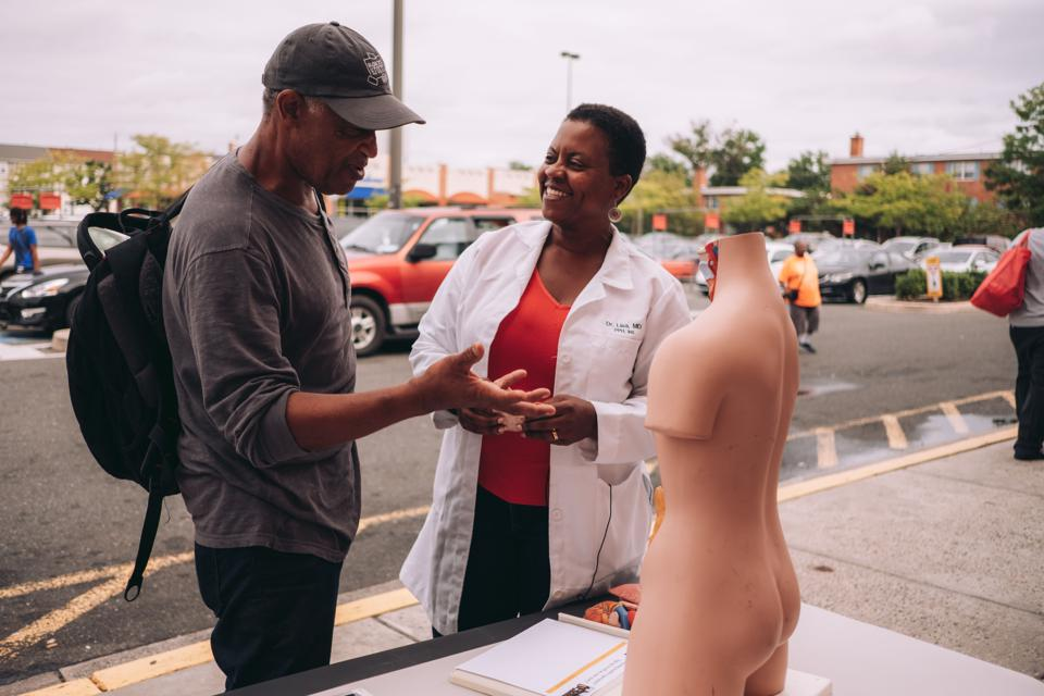 Doctor on the street discussing health with a member of the community