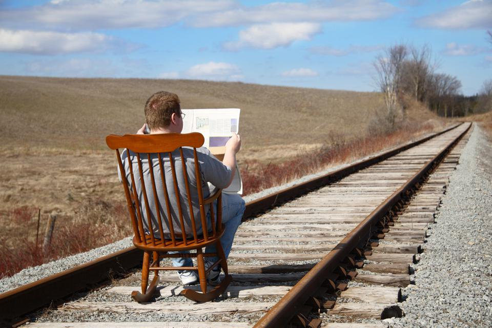 Man reading a peer in a chair on a railroad tack is a good metaphor for complacency.