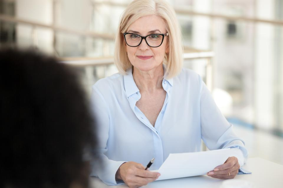 Female business professional at job interview -- how to start over after age 50