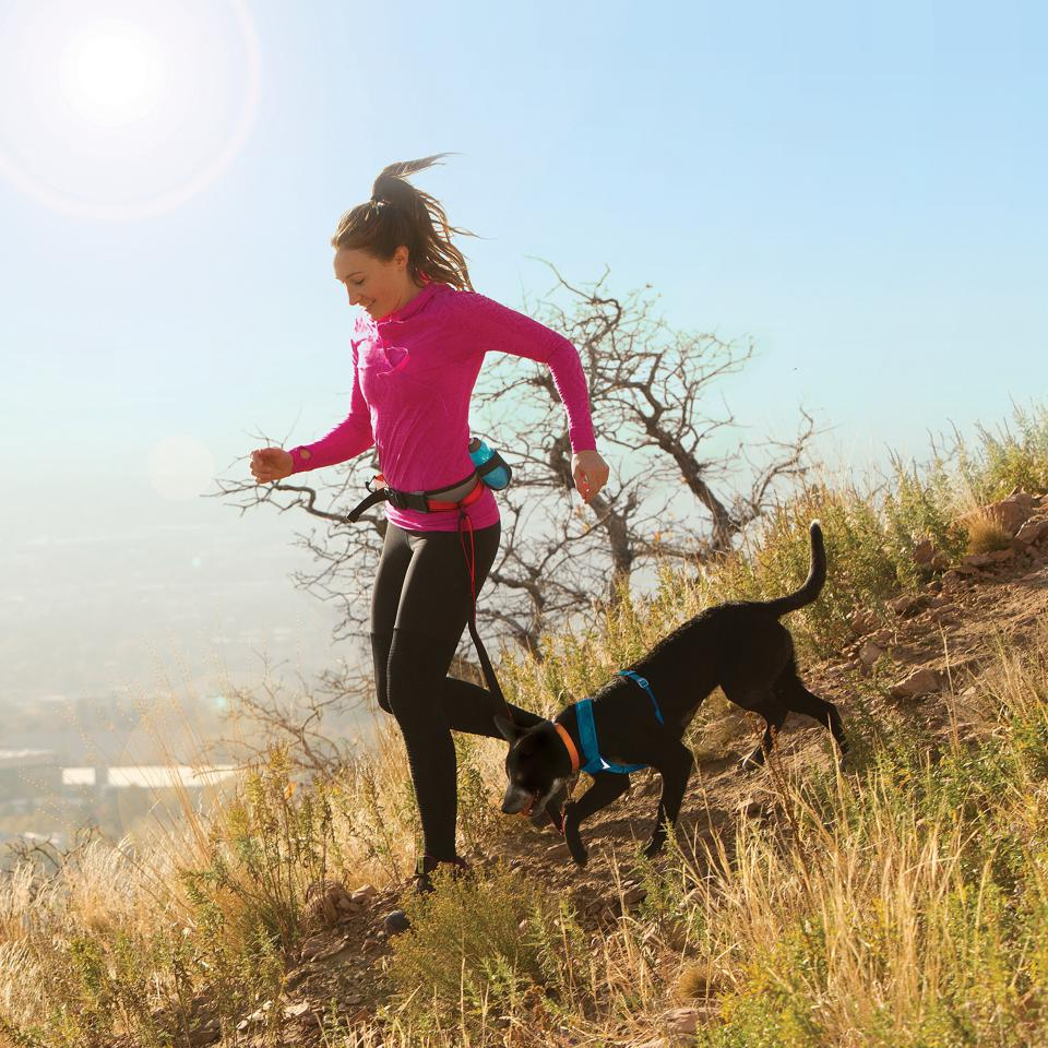 Running with a dog down a hill.