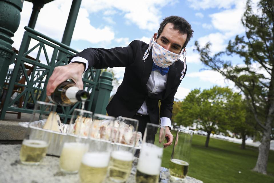 Champagne celebrations are not what they once were - man pours champagne with mask