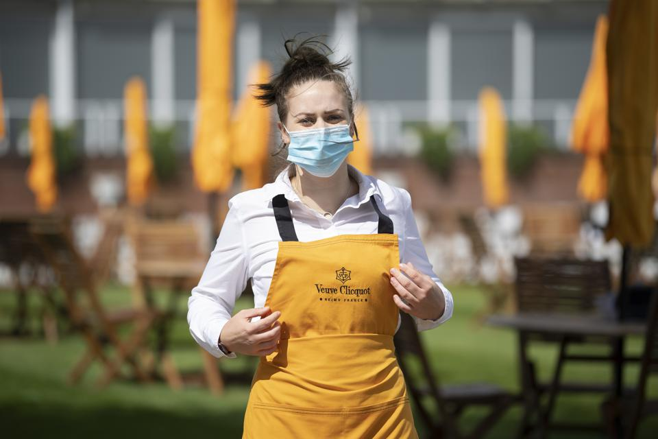 A Waitress wearing a mask on the Champagne lawn during the Goodwood Festival at Goodwood Racecourse, Chichester, U.K.