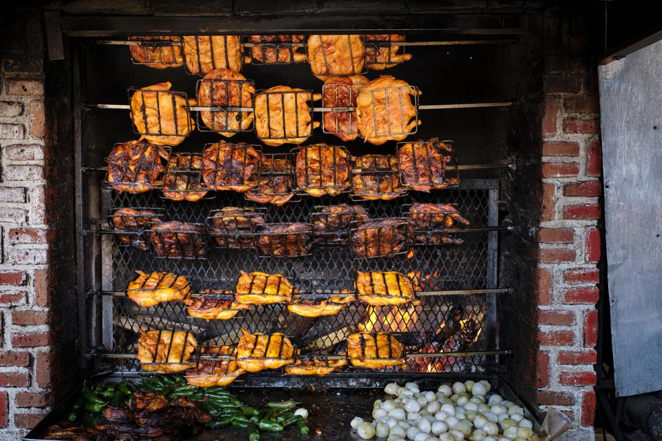 Chickens on the stick roasting in a wood oven in a...