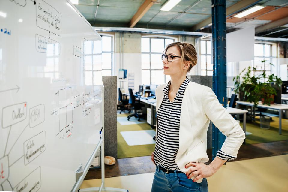 Businesswoman Looking At Whiteboard After Meeting
