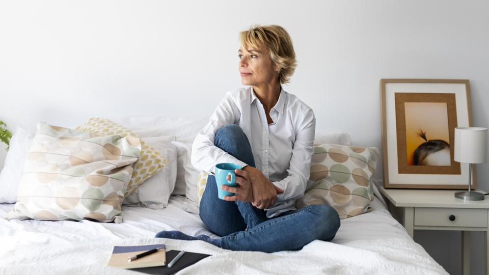 Relaxed mature woman sitting on bed at home