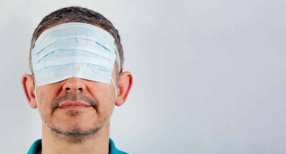 Blindfolded man with surgical mask over the eyes and bare mouth and nose