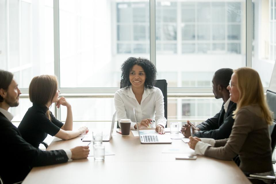 Smiling african american female boss leading corporate diverse team meeting