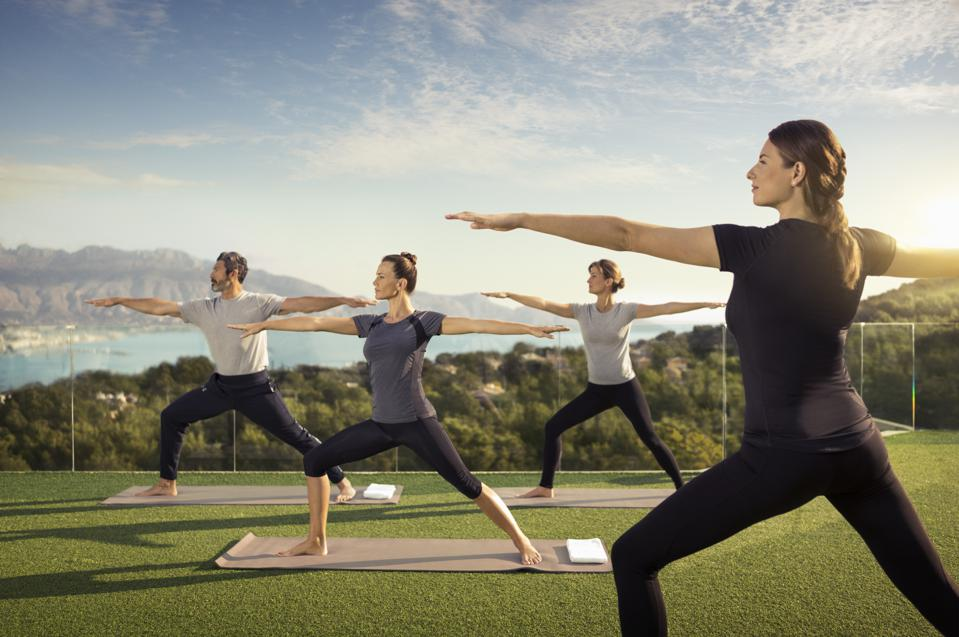 Three women and a man practice yoga outdoors at SHA Wellness Clinic in Spain.