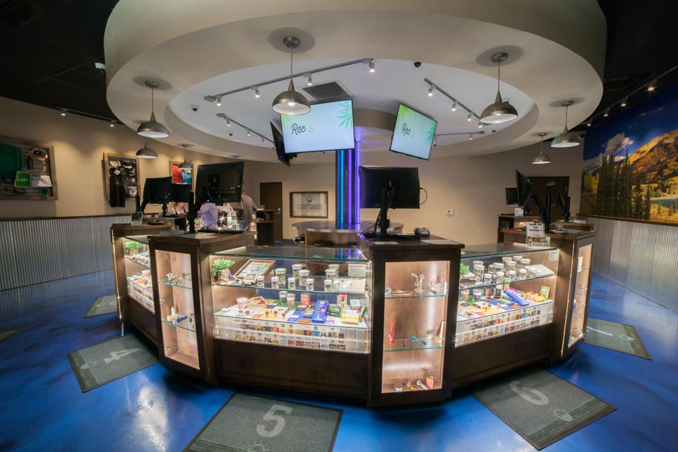 inside of a cannabis shop with a lighted display case of products