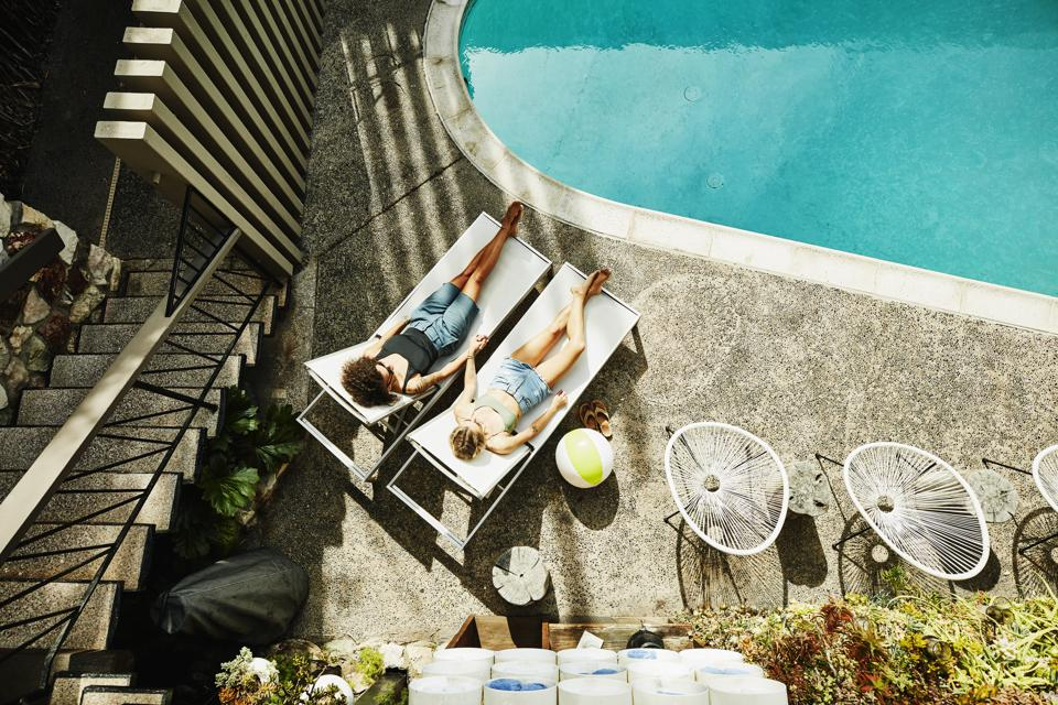 Overhead view of lesbian couple holding hands while relaxing in lounge chairs by hotel pool