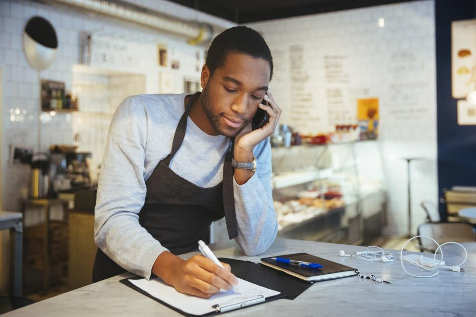 Young male employee talking through smart phone while writing on clipboard at delicatessen