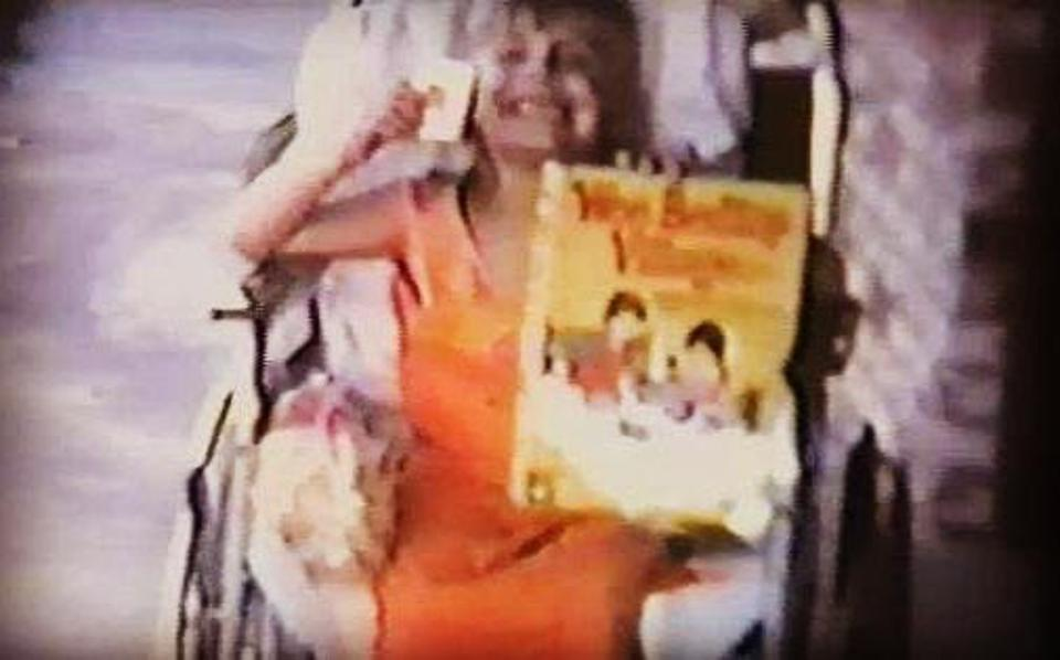 A young Eileen Grubba in a wheelchair and holding a book. She is smiling.