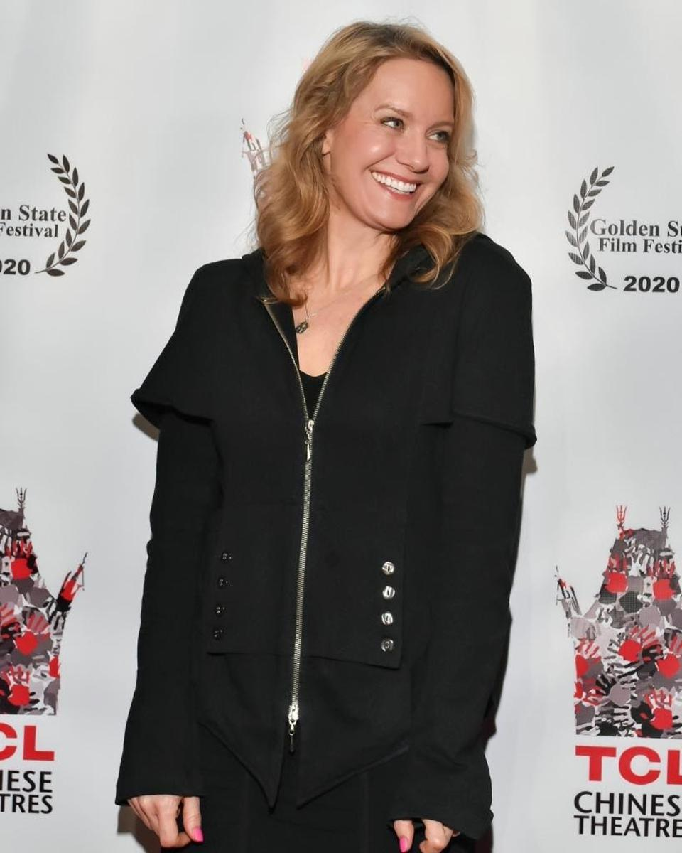 Eileen Grubba, wearing a black shirt and pants, poses for a photo at a festival.