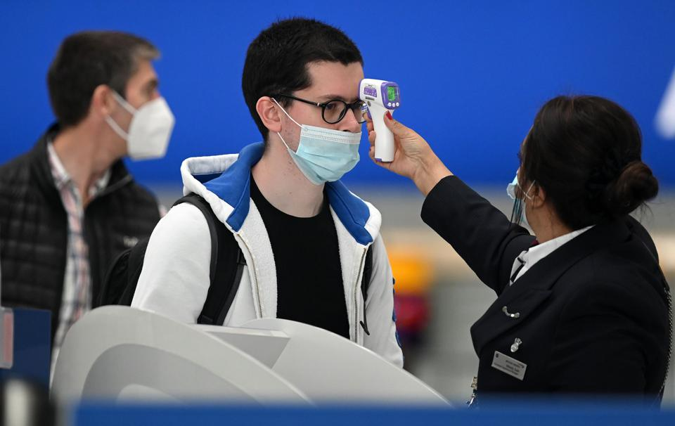 woman at Heathrow airport tests man's temperature for covid on arriving in the U.K.