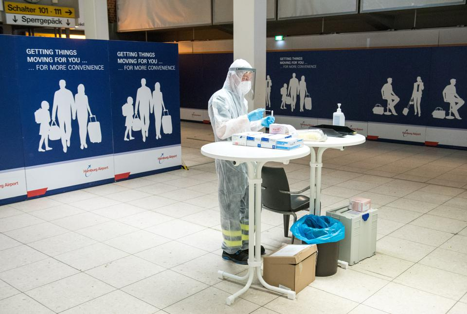 health worker in protective clothing at Corona test centre at Hamburg airport Germany