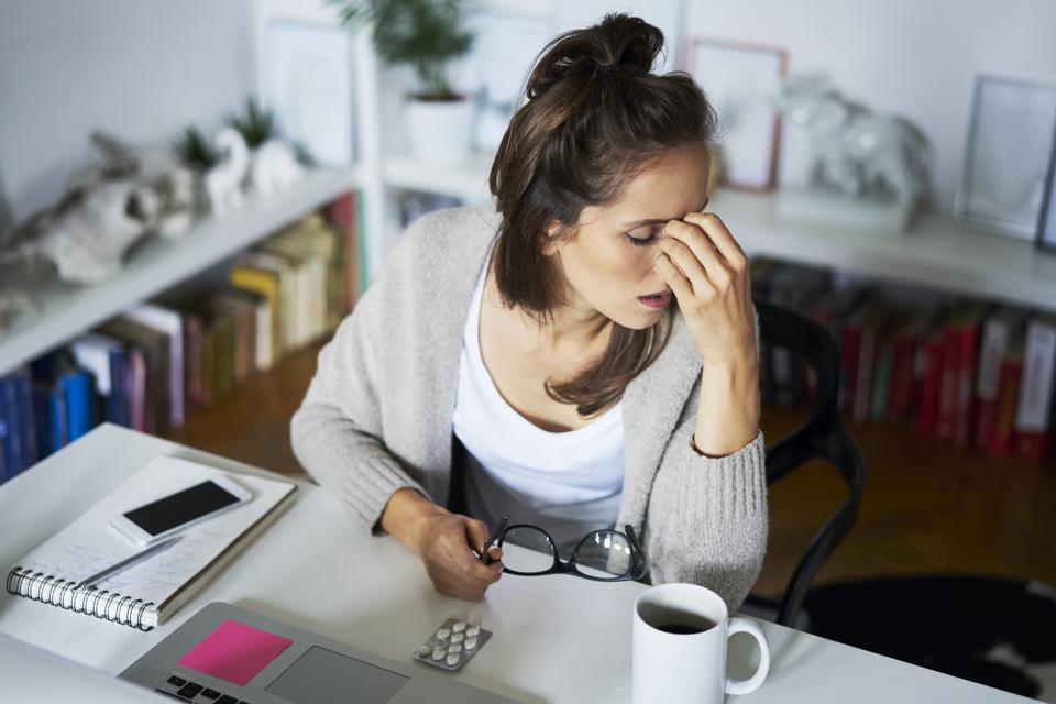 Young woman at home at desk suffering headache