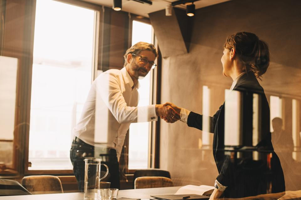 Mature customer shaking hands with female lawyer in meeting