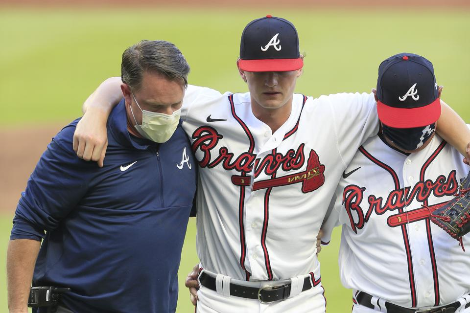 Injured pitcher Mike Soroka is helped off the field.