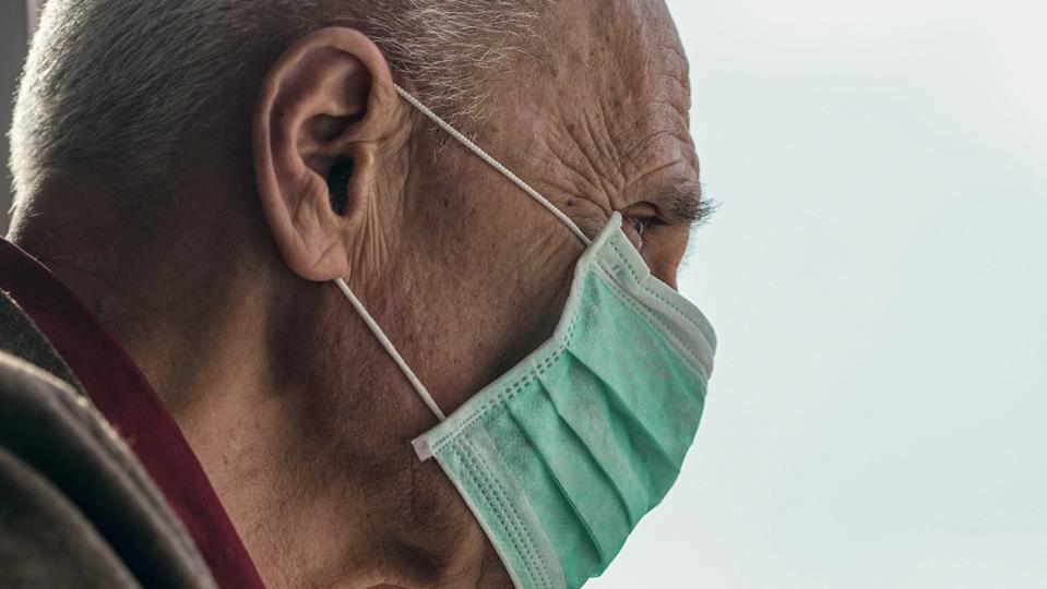 old man wearing medical face mask looking through window blue sky background