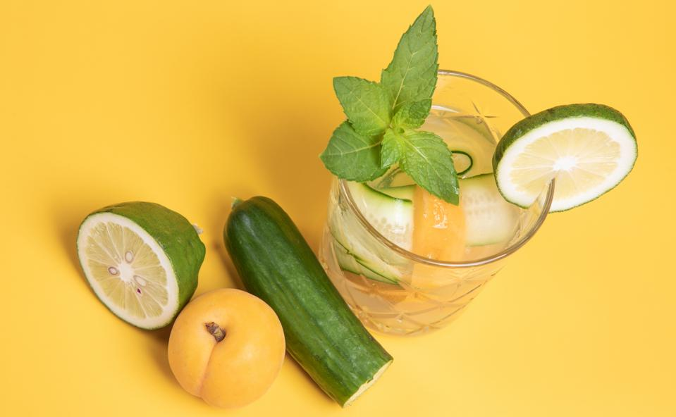 summer cocktail drink with fresh ingredients, cucumber, apricot, lime, mint, citrus