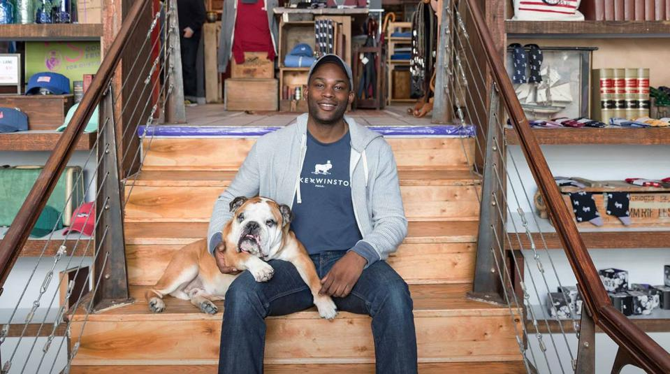 Seun Olubodun, founder of Duke & Winston, sitting on the stairs with his bulldog, Duke.