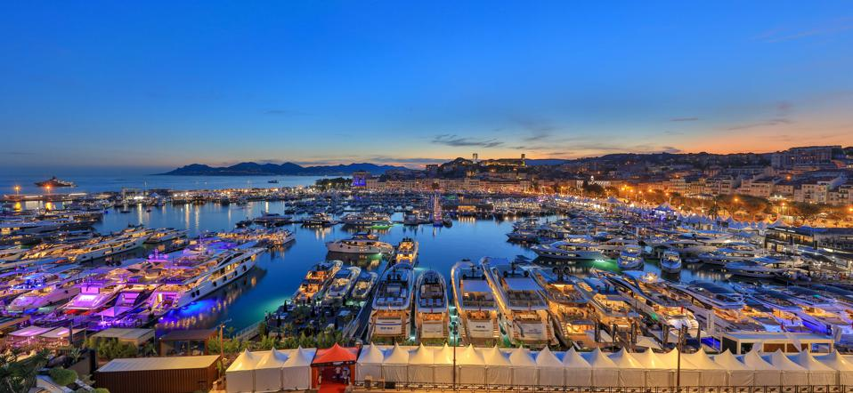 Yachts and sailing boats lit up at night at the Cannes Yachting Festival in France