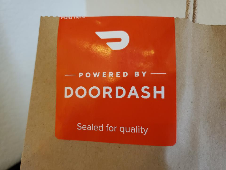 Sticker on takeout bag reading Powered by Doordash, Sealed for Quality