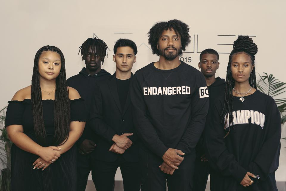 Six people with their arms crossed in front of them, facing the camera, all wearing black.