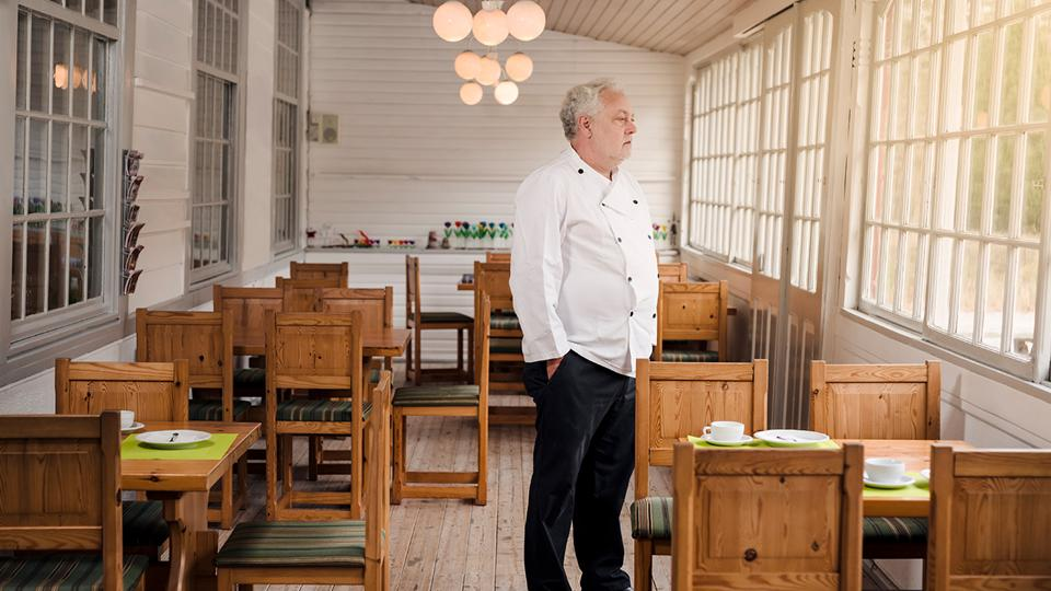 Chef stares out window of his restaurant that has several empty tables all set for clients