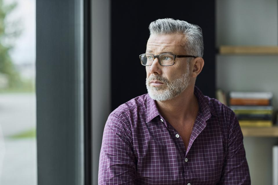 Thoughtful businessman looking away in office
