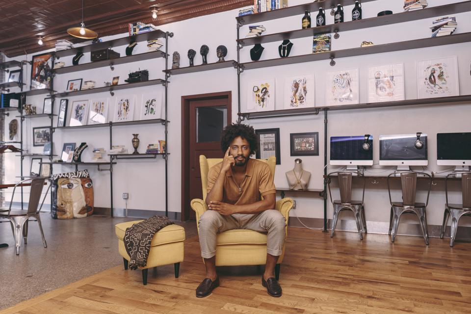 A young man sits in a large room filled with art, looking at the camera.