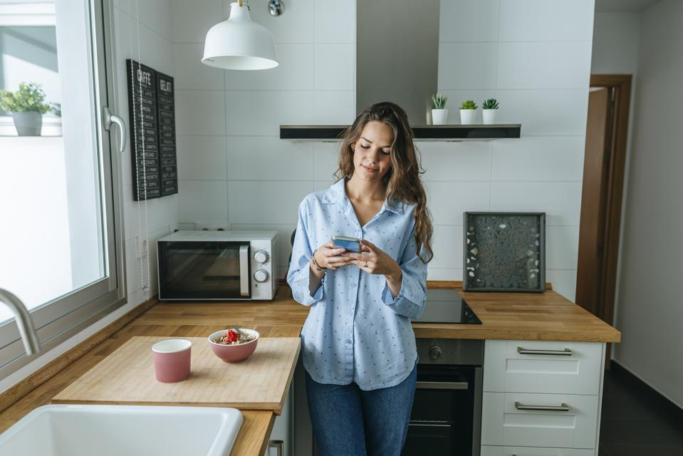 Young woman wearing pyjama in kitchen at home using cell phone