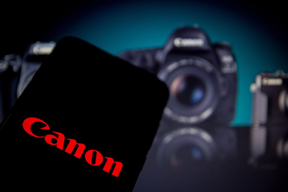 Canon logo in red on a smartphone, with Canon cameras in the background