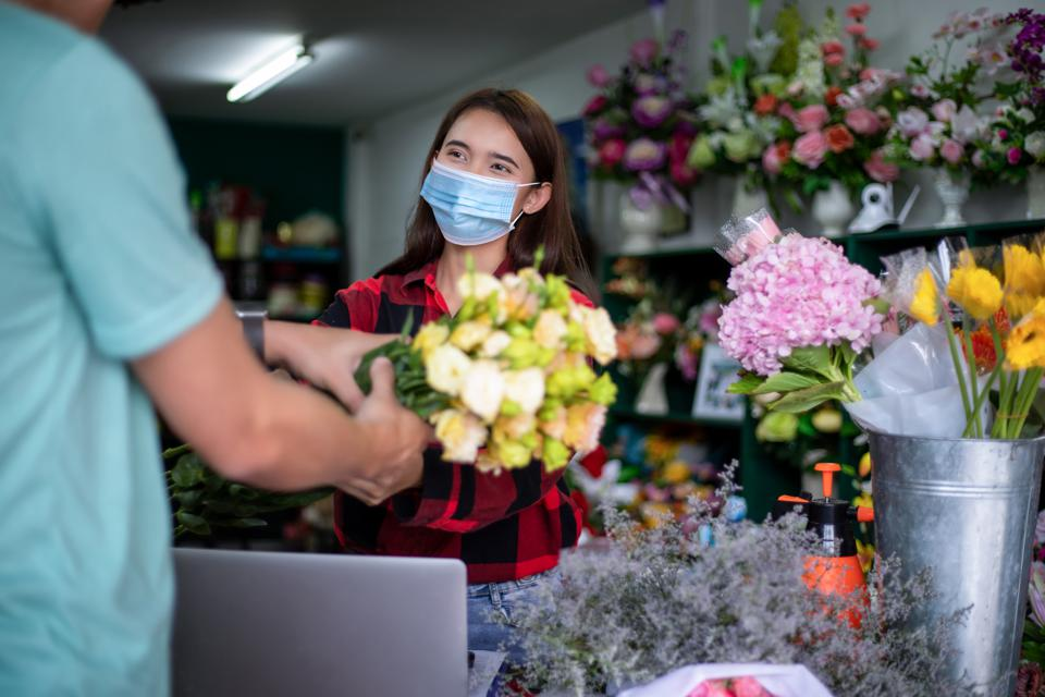 Asian Woman wearing a face mask or protective mask against coronavirus crisis, Florist owner of a small florist business holding flowers for delivery to customers at her store