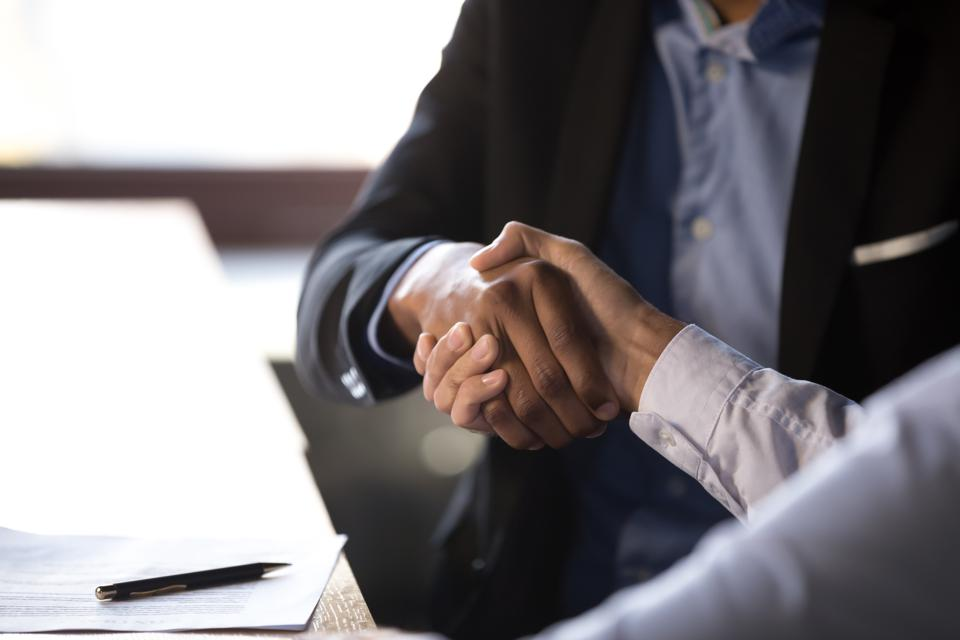 Close up african businessman shaking hands with client