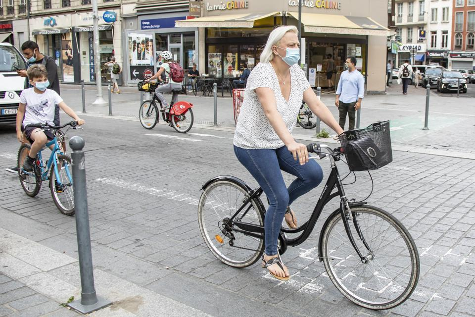 People wearing masks ride on the street in central Lille, northern France, Aug. 3, 2020.