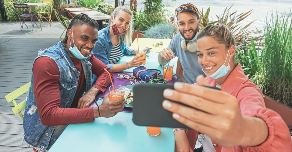 Friends takeing selfie in a bar restaurant with face mask on in coronavirus time - Young people having fun with drinks and snacks outside with new rules after virus break